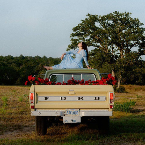 Album cover of Saint Cloud by Waxahatchee, showing a woman sitting on the roof of a pick-up truck with red flowers in the bed of the truck.